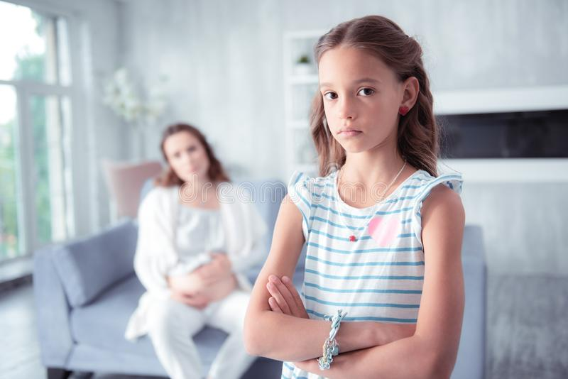 Dark-eyed daughter having no wish to talk to her pregnant mother stock images