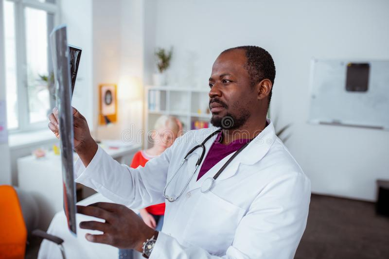 Dark-eyed doctor feeling concerned while checking x-ray of girl stock images