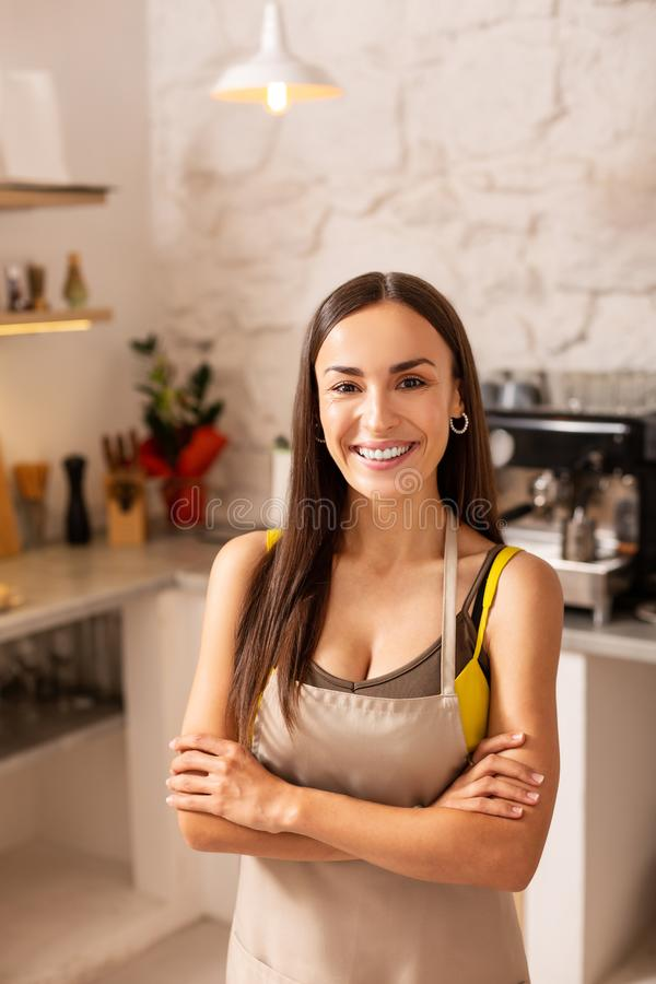 Dark-eyed entrepreneur standing in her coffeehouse royalty free stock image