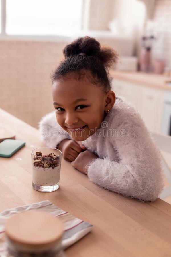Dark-eyed girl feeling cheerful while having dessert at home royalty free stock photo