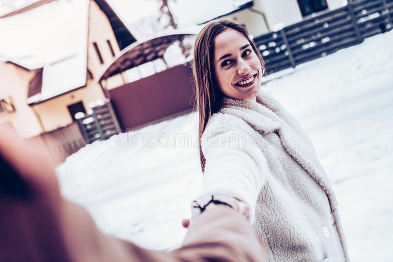 Dark-eyed girlfriend taking her man out of house for enjoying winter stock image