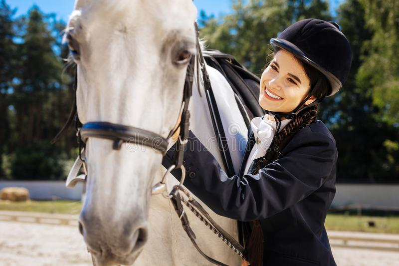 Dark-eyed horsewoman with long braid feeling contended. Contended horsewoman. Dark-eyed horsewoman with long braid feeling contended after nice horse racing stock images