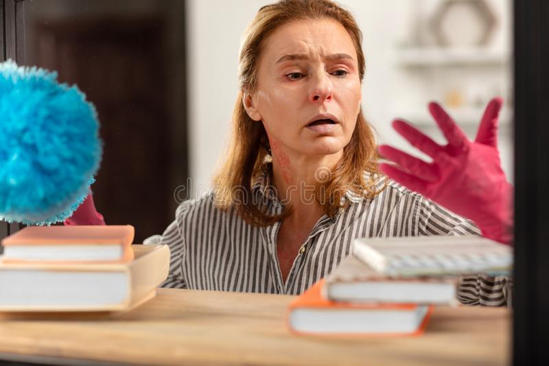 Dark-eyed housewife wearing pink gloves feeling tired of dust royalty free stock image