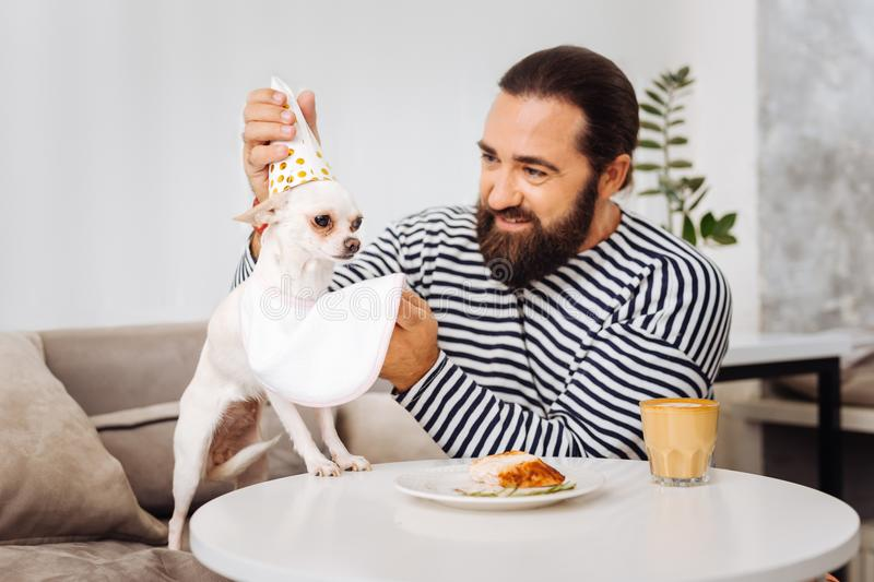 Dark-eyed mature man feeling great love for pets stock photo