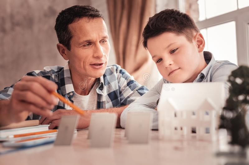 Dark-eyed schoolboy and his father building model of separate house. Building model. Dark-eyed smart schoolboy and his caring loving father building model of stock image
