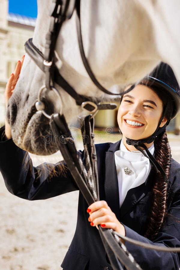 Dark-eyed smiling female rider coming to race track on her day off. Day off. Dark-eyed smiling female rider fond of equestrianism coming to race track on her day royalty free stock photos