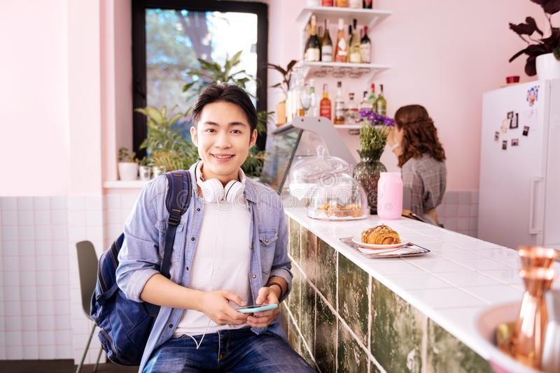 Dark-eyed student with earphones on his neck coming to cafe. Earphones on neck. Dark-eyed student with earphones on his neck coming to cafe while running late royalty free stock photo