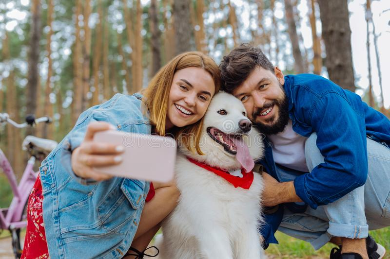 Dark-eyed white dog posing for photo with his owners royalty free stock photo