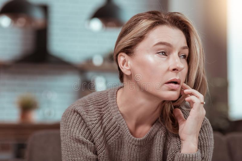 Dark-eyed wife feeling frustrated after argument with husband. Frustrated after argument. Dark-eyed mature appealing wife feeling frustrated after argument with royalty free stock image