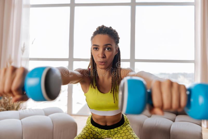 Dark-eyed woman breathing actively while sitting up with barbells stock photos