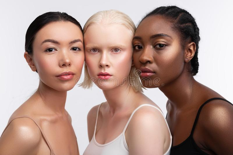 Blonde woman with bob cut standing between dark-eyed women stock photo
