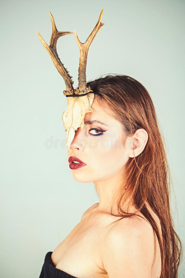 Dark fantasy creature elf on halloween in skull. Woman with makeup and antlers. Fashion devil of mystic shaman girl with. Horns. Beauty look and cosmetics for stock photos