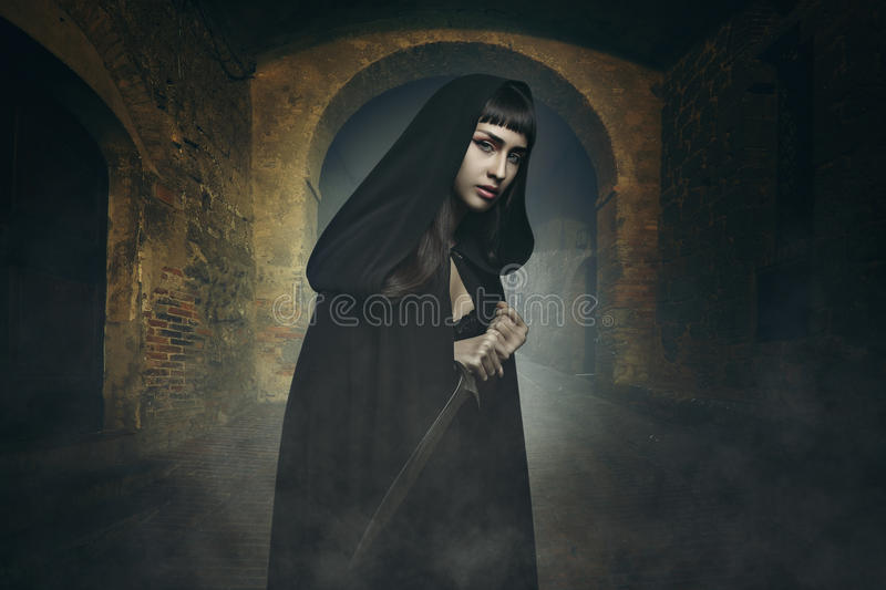 Dark fantasy thief. Dark beautiful thief in a stone village . Fantasy and halloween concept royalty free stock images