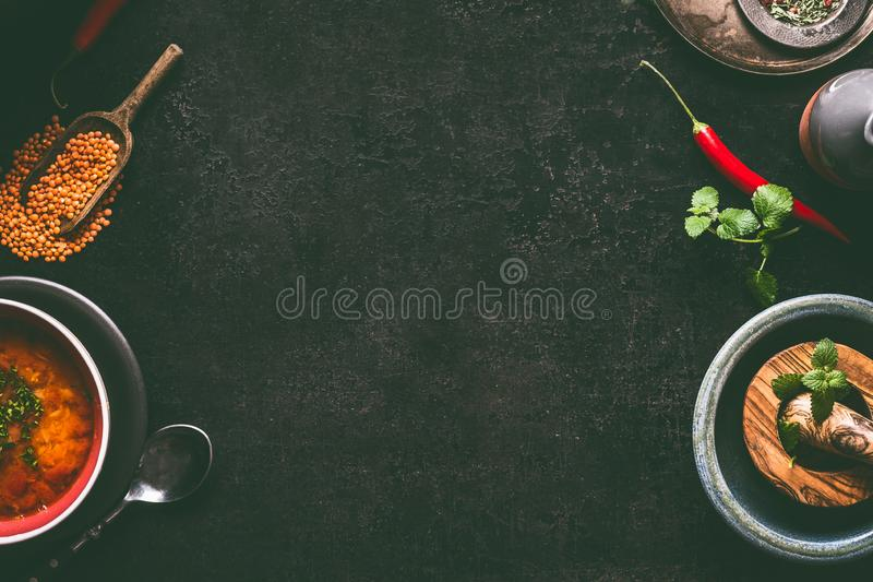 Dark food background with hot lentil soup and cooking ingredients, top view, frame. Healthy vegan eating. Concept stock image