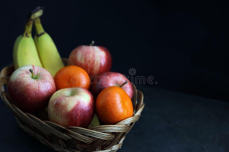 Dark Food - Chiaroscuro mixed fruit in wicker basket stock image