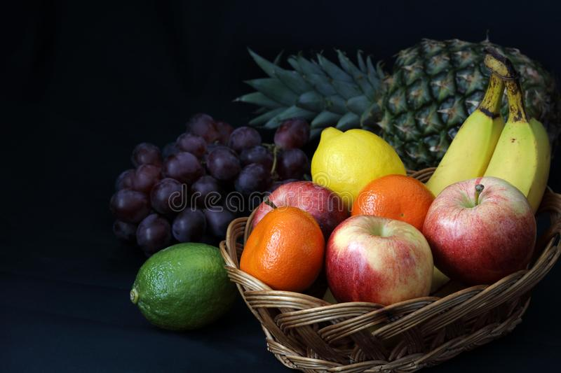 Dark Food - Chiaroscuro mixed fruit in wicker basket royalty free stock photo