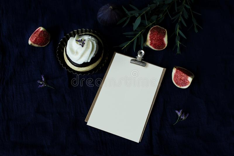 Dark food still life. Ripe purple figs on linen tablecloth. Greeting card mockup in binder clip. Vintage moody stock photography