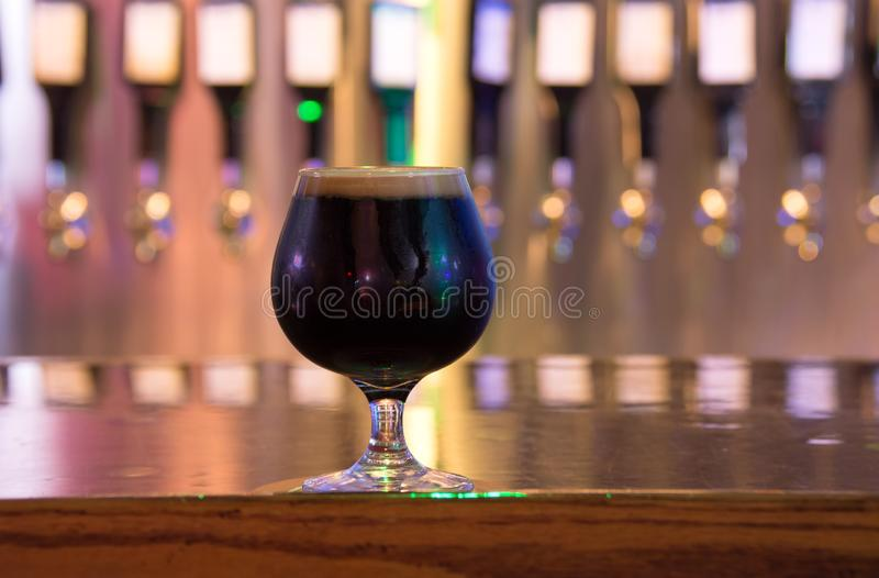 Dark full flavor stout style Belgian craft beer with smooth frothy head of foam with row of beer taps in the background royalty free stock photos