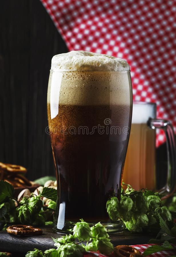 Dark German beer is poured into a glass, fresh green hops and bowls with salty snacks and nuts, autumn beer festival concept, dark. Background, selective focus stock photo