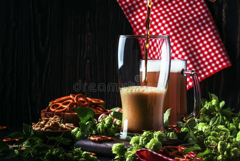 Dark German beer is poured into a glass, fresh green hops and bowls with salty snacks and nuts, autumn beer festival concept, dark royalty free stock photography