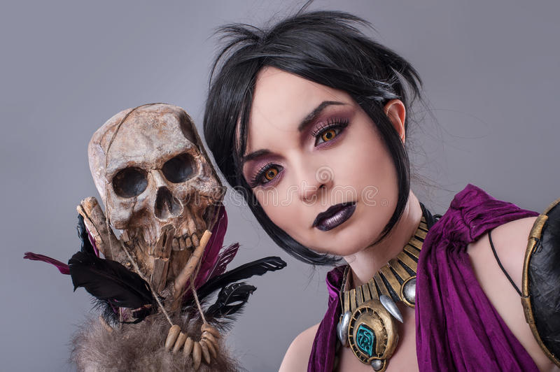 Dark gothic woman. Gothic woman posing with skull royalty free stock photo
