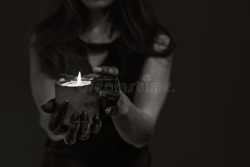 Dark gothic young woman in witch halloween costume with makeup and hand over black background with candle, isolated. Dark gothic young woman in witch halloween royalty free stock photography