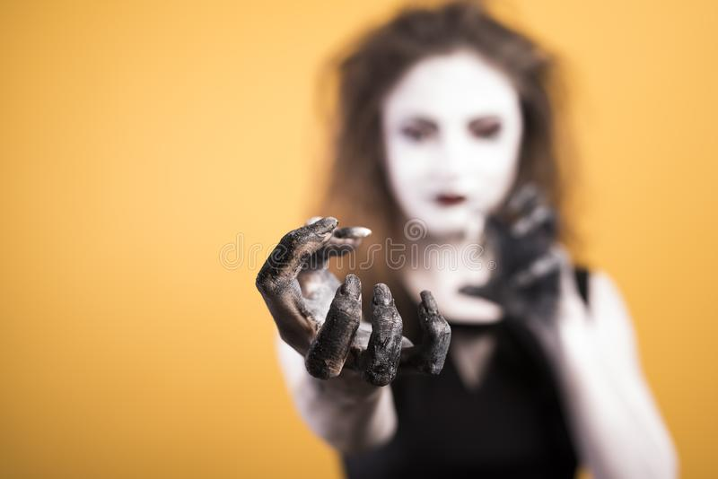 Dark gothic young woman in witch halloween costume with makeup and hanf over yellow background. A lot of clean space, copyspace royalty free stock photo