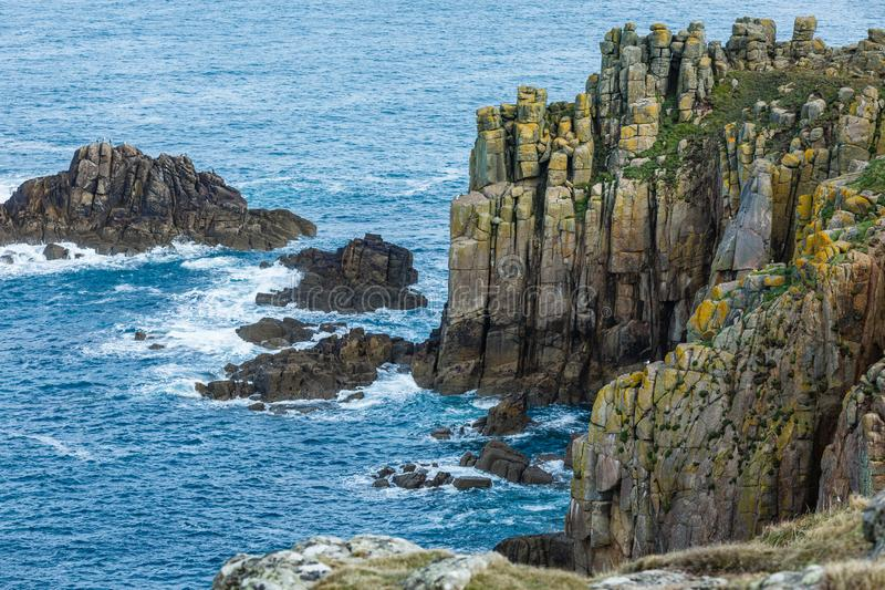 Dark, gray steep cliffs by the sea. Where only the grass grows; a blue sea with white waves on rocky shores and a small island; sea landscape royalty free stock image