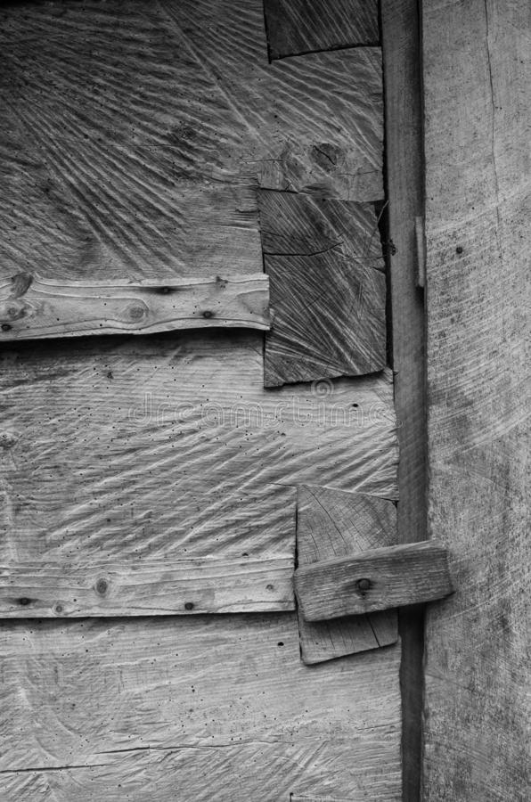 Dark gray weathered rustic rural wooden barn wall, door, gate, primirive lock timber planks closeup texture background. Empty. Sapce for text, lettering, copy royalty free stock photography