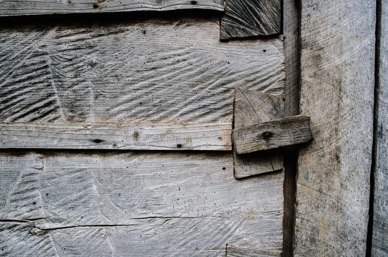 Dark gray weathered rustic rural wooden barn wall, door, gate, primirive lock timber planks closeup texture background. Empty. Sapce for text, lettering, copy stock image
