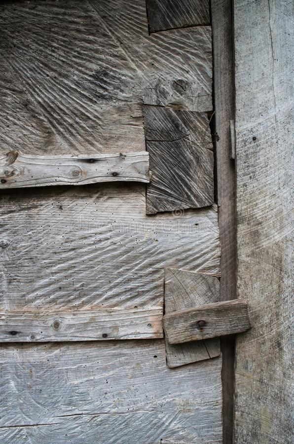 Dark gray weathered rustic rural wooden barn wall, door, gate, primitive lock timber planks closeup texture background. Empty. Space for text, lettering, copy stock images