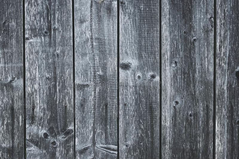 Dark gray wood fence. Shabby table. Old grey wooden boards. Pattern of cracked planks. Strips on wood surface. Dilapidated boards. With nails. Grunge texture royalty free stock image