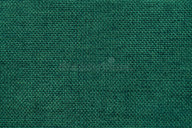 Dark green background of dense woven bagging fabric, closeup. Structure of the textile macro. Dark green shiny background of dense woven bagging fabric, closeup royalty free stock image