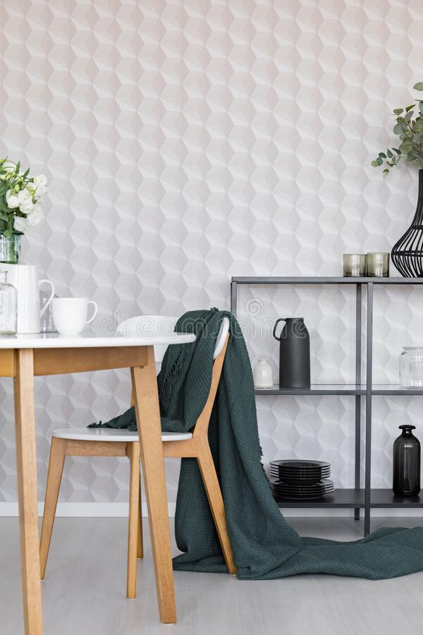 Dark green blanket on wooden chair next to table in stylish dining room interior with metal shelf with plates and jugs and. Geometric wallpaper royalty free stock images