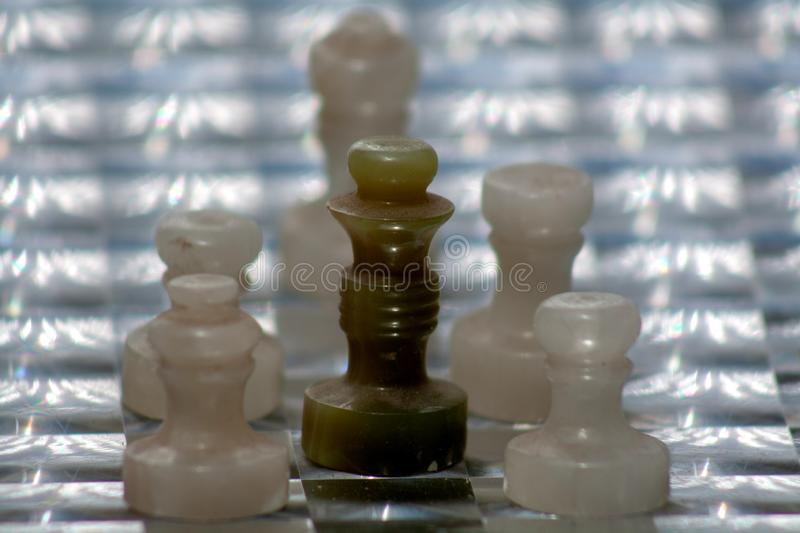 Dark green chess queen. In creative combination with white figures on the original board. Beautiful photo for background images stock photo