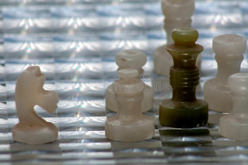 Dark green chess queen. In creative combination with white figures on the original board. Beautiful photo for background images royalty free stock images