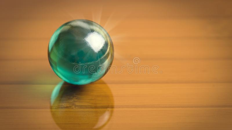 Dark green glass sphere on the reflect dark glass surface. Free place for your text or image. stock photo