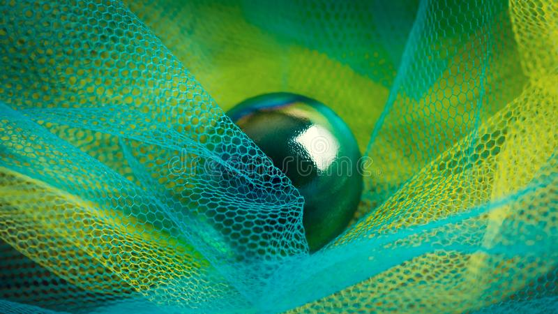 Dark green glass sphere in the yellow and blue plastic fishnets. Abstract high resolution macro photography. royalty free stock photo