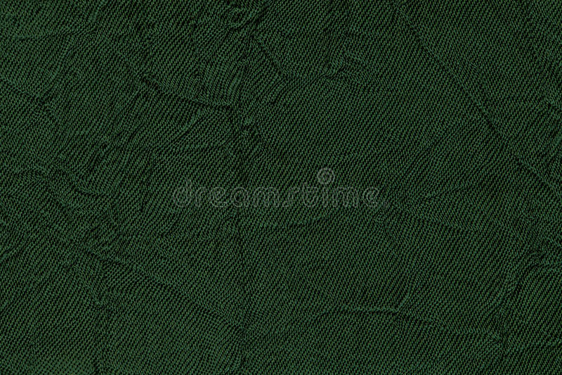 Dark green wavy background from a textile material. Fabric with fold texture closeup. Creased shiny emerald cloth stock image