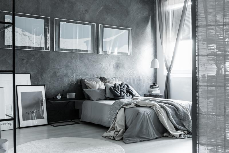 Dark grey bedroom with screen. Screen and posters in dark grey bedroom with bedsheets on king-size bed against textured wall royalty free stock images