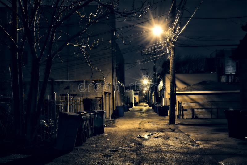 Dark, gritty and wet Chicago alley at night after rain. Dark gritty and wet Chicago alley at night after rain royalty free stock images