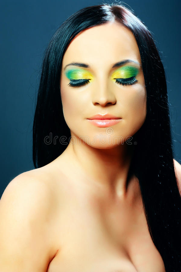 Dark hair woman showing makeup on his eyes. Dark hair woman showing green yellow makeup on his closed eyes and beauty face, studio shot on dark background stock photos