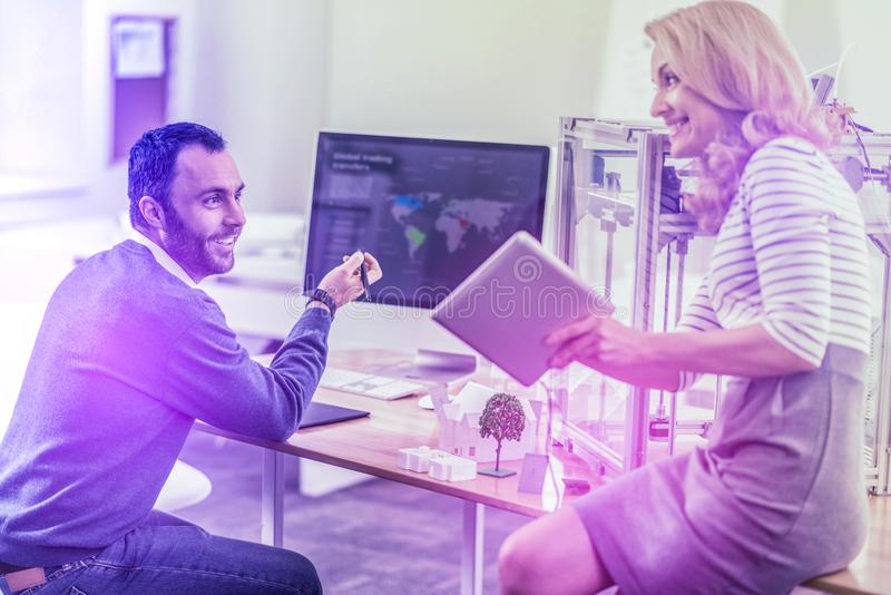 Dark-haired bearded office worker helping his colleague using 3D printer. Helpful worker. Dark-haired bearded office worker helping his colleague using 3D royalty free stock photography