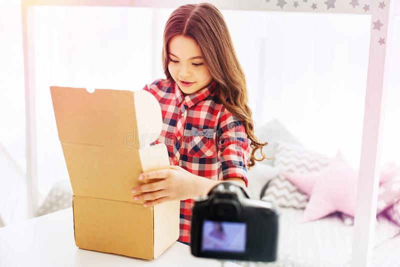Dark-haired beautiful schoolgirl opening the box with presents in her light room royalty free stock photo