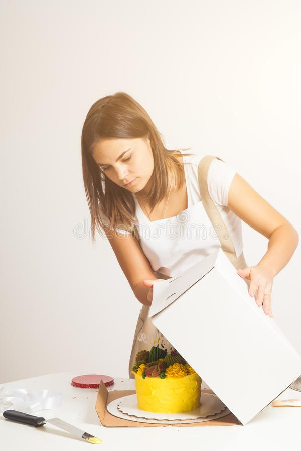 Confectioner pack cake. Dark-haired, beautiful woman confectioner, a pastry shopper in a white T-shirt and beige apron, packs a homemade yellow cake in a royalty free stock photo