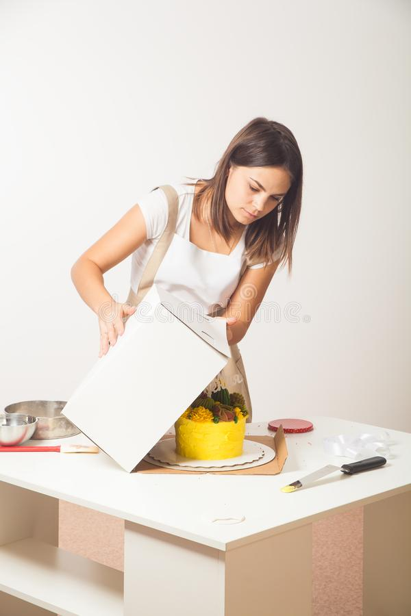 Confectioner pack cake. Dark-haired, beautiful woman confectioner, a pastry shopper in a white T-shirt and beige apron, packs a homemade yellow cake in a stock photography