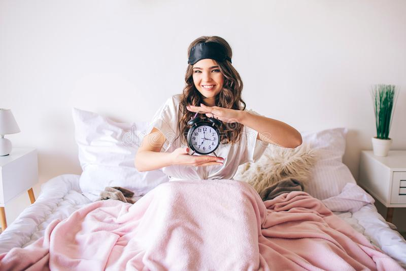 Dark haired beautiful young brunette wake up in her bed. Cheerful nice woman holding clock in hands and smile. Look stock photos