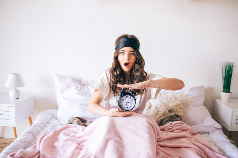 Dark haired beautiful young brunette wake up in her bed. Confused woman hold clock in hands. Woke up later. Amazed model stock photo