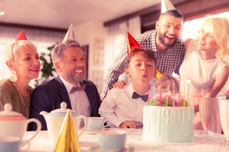 Dark-haired birthday boy blowing candles on his yummy cake royalty free stock images
