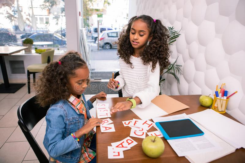 Dark-haired curly sisters feeling joyful while studying together in kids cafe royalty free stock photos